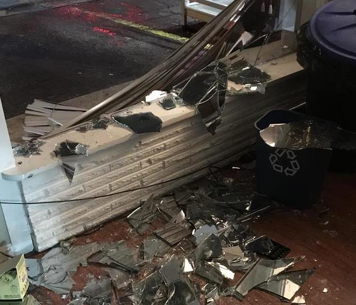 Local business with front window broke out, glass and debris strung through the inside