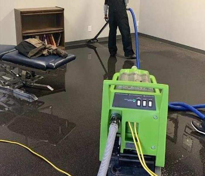 Technician extracting water from a tile floor in a house flooded due to a burst pipe.